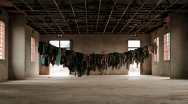 clothes of murdered rwandans in a memorial - by shawna nelles